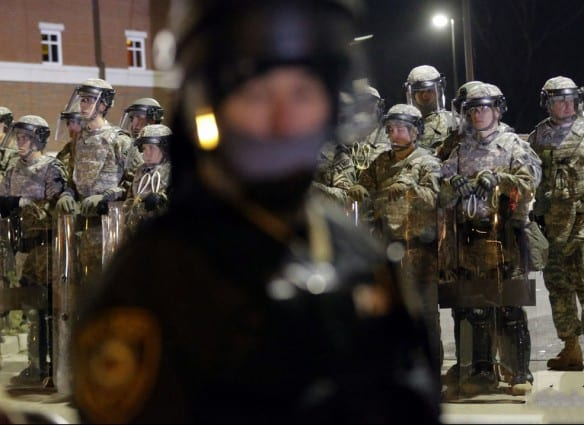 Missouri National Guard line up behind police officers monitoring protesters in front of the Ferguson Police Department Tuesday, Nov. 25, 2014, in Ferguson, Mo. Missouri's governor ordered hundreds more state militia into Ferguson on Tuesday, after a night of protests and rioting over a grand jury's decision not to indict police officer Darren Wilson in the fatal shooting of Michael Brown, a case that has inflamed racial tensions in the U.S.