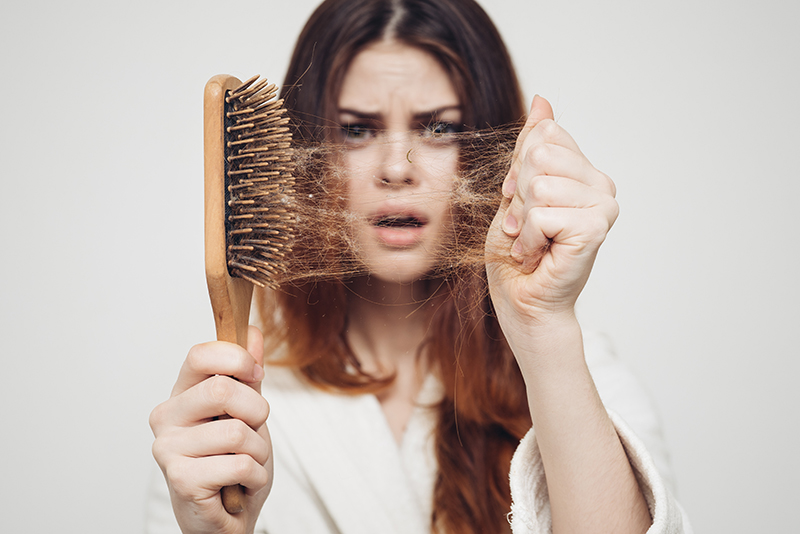 woman holding a brush full of lost hair